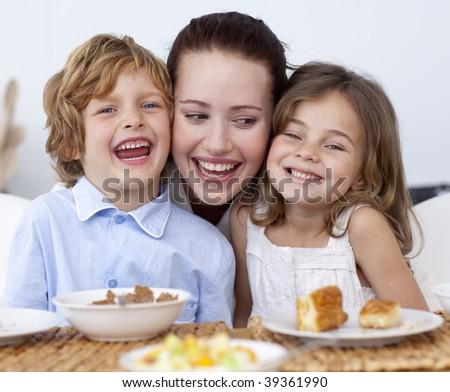 Children having breakfast in kitchen with their mother - stock photo