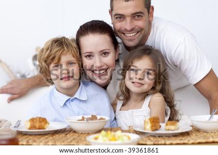 Children having breakfast in kitchen with their parents - stock photo