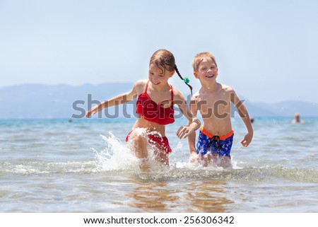 Children having fun in the sea - stock photo