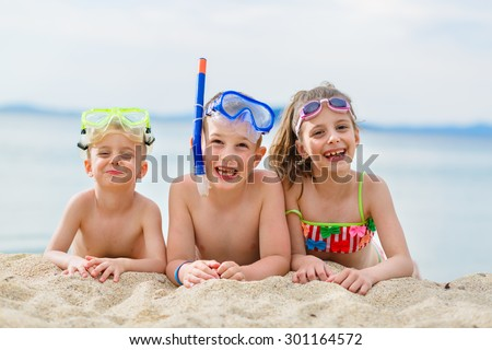 Children having fun on the beach getting ready to go scuba diving - stock photo