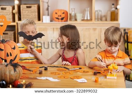Children having fun when making Halloween decorations - stock photo