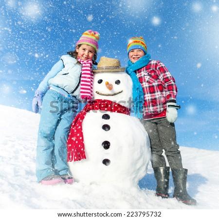 Children having fun with a Snowman.  - stock photo