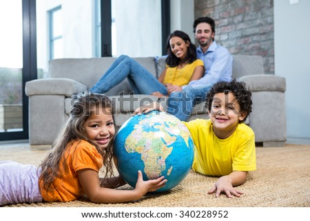 Children holding globe on carpet while parents on sofa in living room - stock photo