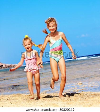 Children holding hands running on  beach. - stock photo