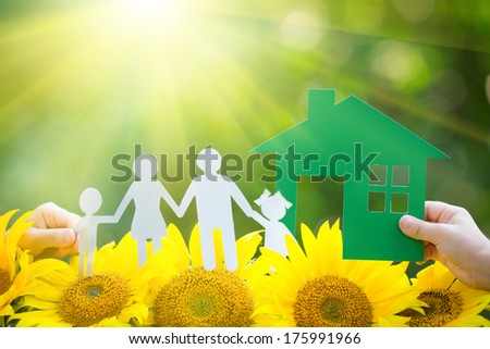 Children holding paper house and family in hands outdoors
