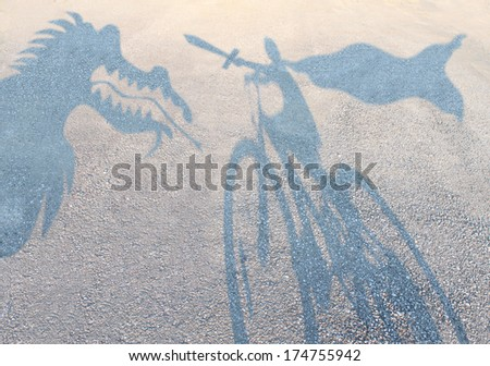 Children imagination concept with cast shadows on a gravel floor of a superhero child wearing a cape on a bicycle slaying an imaginary dragon as a metaphor for kids story book  dreams of fairy tales. - stock photo