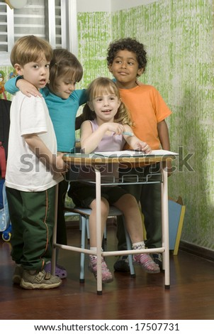 Children in a classroom.  They are smiling and have their arms around each other.  Vertically framed shot. - stock photo
