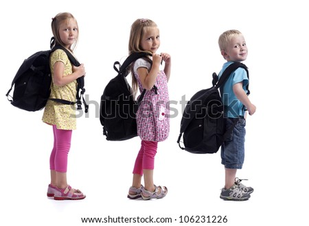 children in a row with backpacks. Isolated on white background - stock photo