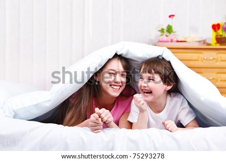 Children in bed, laughing - stock photo