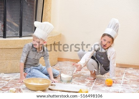 Children in chef's hats near the fireplace: beautiful 6 years old girl dressed in a toque sitting and playing cook with her blue eyed cousin, they are totally stained with flour