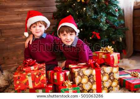 Children in Christmas hat with presents in a house near the Christmas tree.