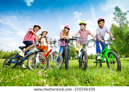 Children in colorful helmets hold their bikes - stock photo