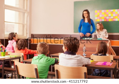 Children in elementary school active learning in classroom with yong teacher . Teacher is in the background in front of chalkboard with one of student..