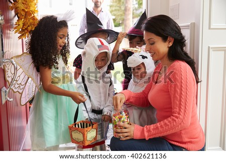 Children In Halloween Costumes Trick Or Treating - stock photo