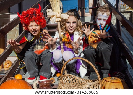children in halloween costumes with pumpkin sit on the stairs - stock photo