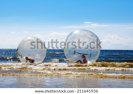 Children in inflatable attraction on the sea - stock photo