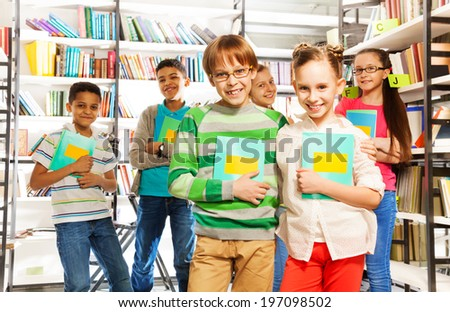 Children in library hold exercise books and stand