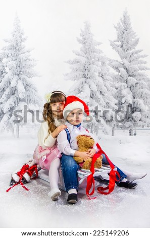 Children in sledge sit in the winter wood - stock photo