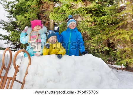 Children in snow fortress play snowball fight - stock photo
