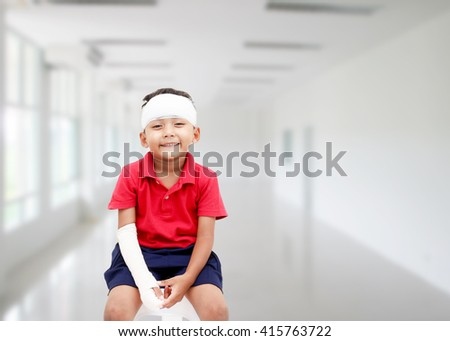 Children injured smile and showing his broken arm and bandaged at head. - stock photo