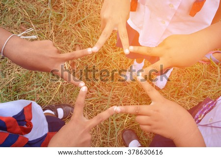 Children join forces to form a star. - stock photo