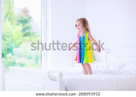 Children jump on a bed. Cute little girl jumping and dancing in a sunny white bedroom. Kids room with garden view window. Toddler kid on a summer morning. Bedding and textile for baby and child. - stock photo