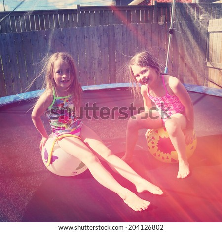 Children jumping on a trampoline in summer in there back yard - stock photo