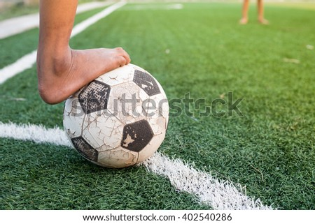 children kicking football on the sports field  - stock photo
