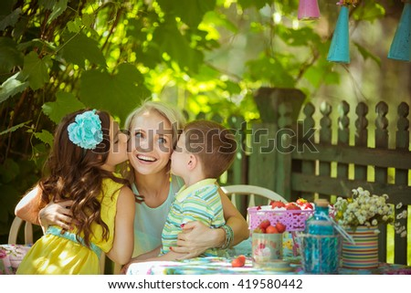 Children kisses his mother in the garden - stock photo