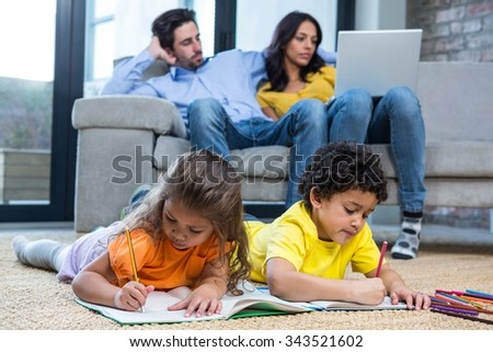 Children laying on the carpet drawing in living room while parents on sofa using laptop - stock photo