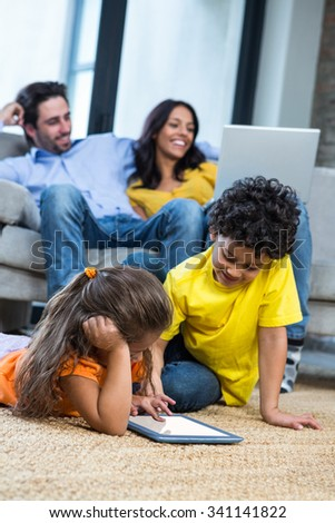 Children laying on the carpet using tablet in living room while parents on sofa using laptop - stock photo