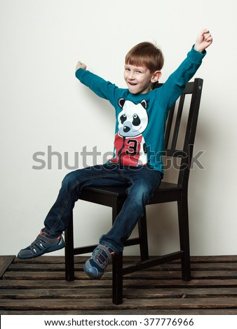Children. Little funny  boy is sitting on the chair, hands up, smiling, hooray gestures  - stock photo