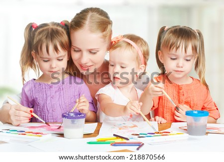 children little twin sisters draw paints with her mother in kindergarten - stock photo