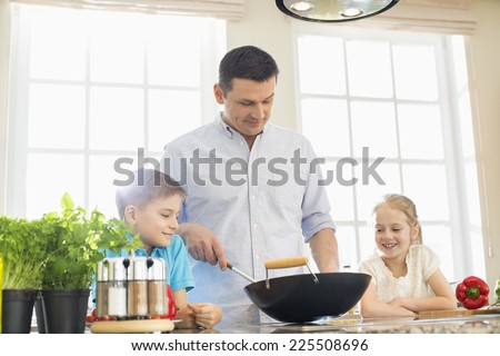 Children looking at father preparing food in kitchen - stock photo
