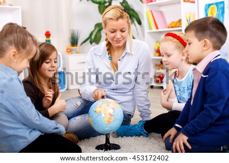 Children looking at globe while listening to teacher during geography lesson - stock photo