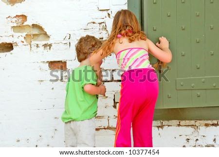 Children Looking Into Door - stock photo