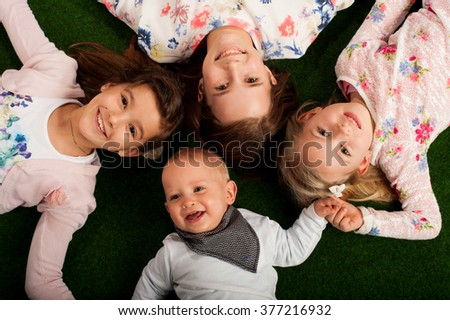 Children lying in grass with heads together. Horizontally framed shot. Happy kids! Adorable - stock photo
