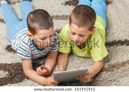 Children lying in the floor and using a tablet  - stock photo