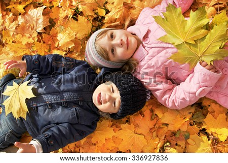children lying on autumn leaves - stock photo