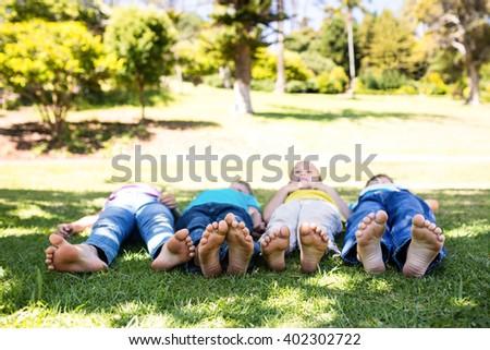 Children lying on grass in park - stock photo
