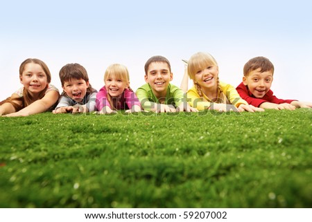 Children lying on green grass - stock photo