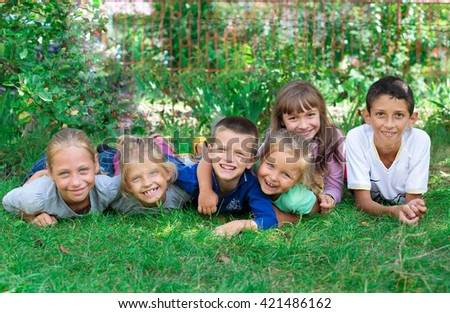 children lying on the grass laughing and having fun Image of happy boys and girls lying on a green grass