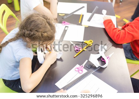 children make crafts out of paper with scissors - stock photo