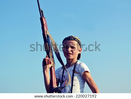 Children of war. Young boy dressed like a soldier with a gun. - stock photo