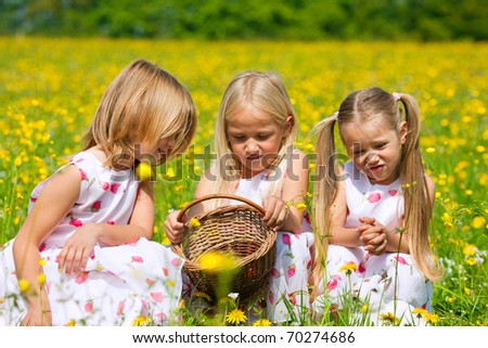 Children on an Easter Egg hunt on a meadow in spring - stock photo
