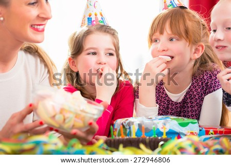 Children on birthday party nibbling candies wearing party hats - stock photo
