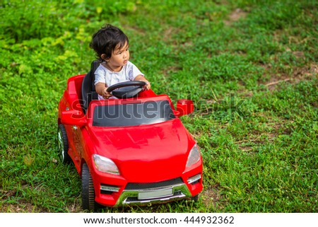 Children on car toy in a meadow on green