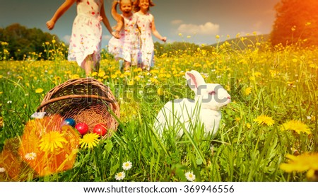 Children on egg hunt for Easter with rabbit on meadow - filtered image - stock photo