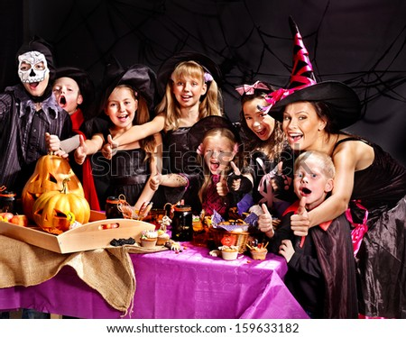 Children on Halloween party  making carved pumpkin - stock photo