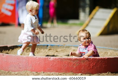 Children on playground in sandbox boy and girl - stock photo